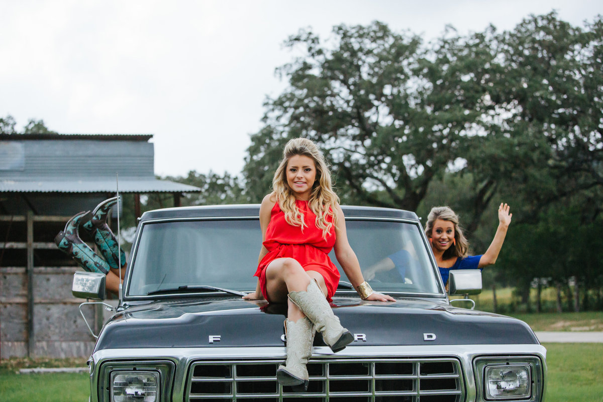 three high school senior girls sitting on truck by San Antonio senior photographer