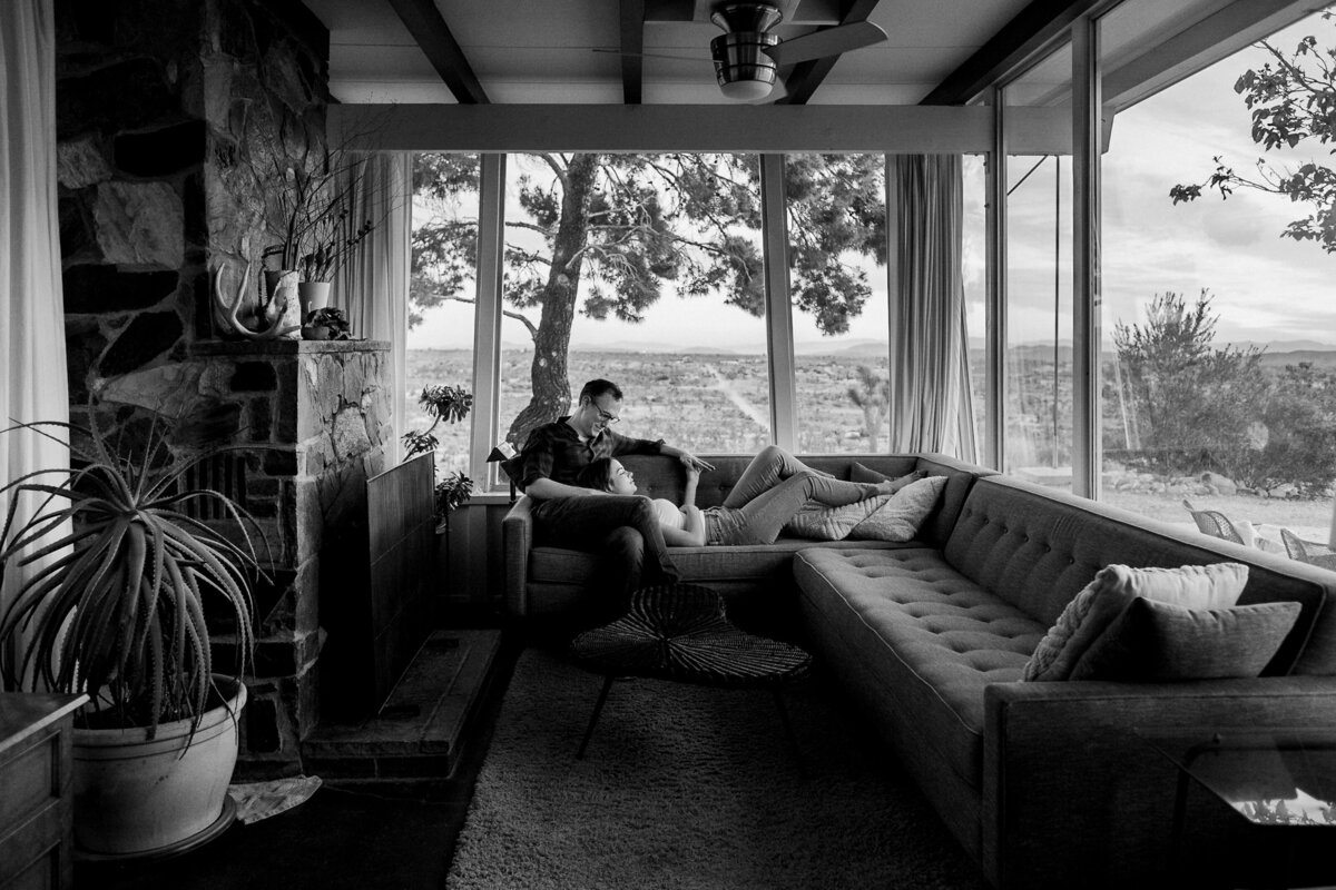 couple embracing on couch while looking out large windows into the desert black and white