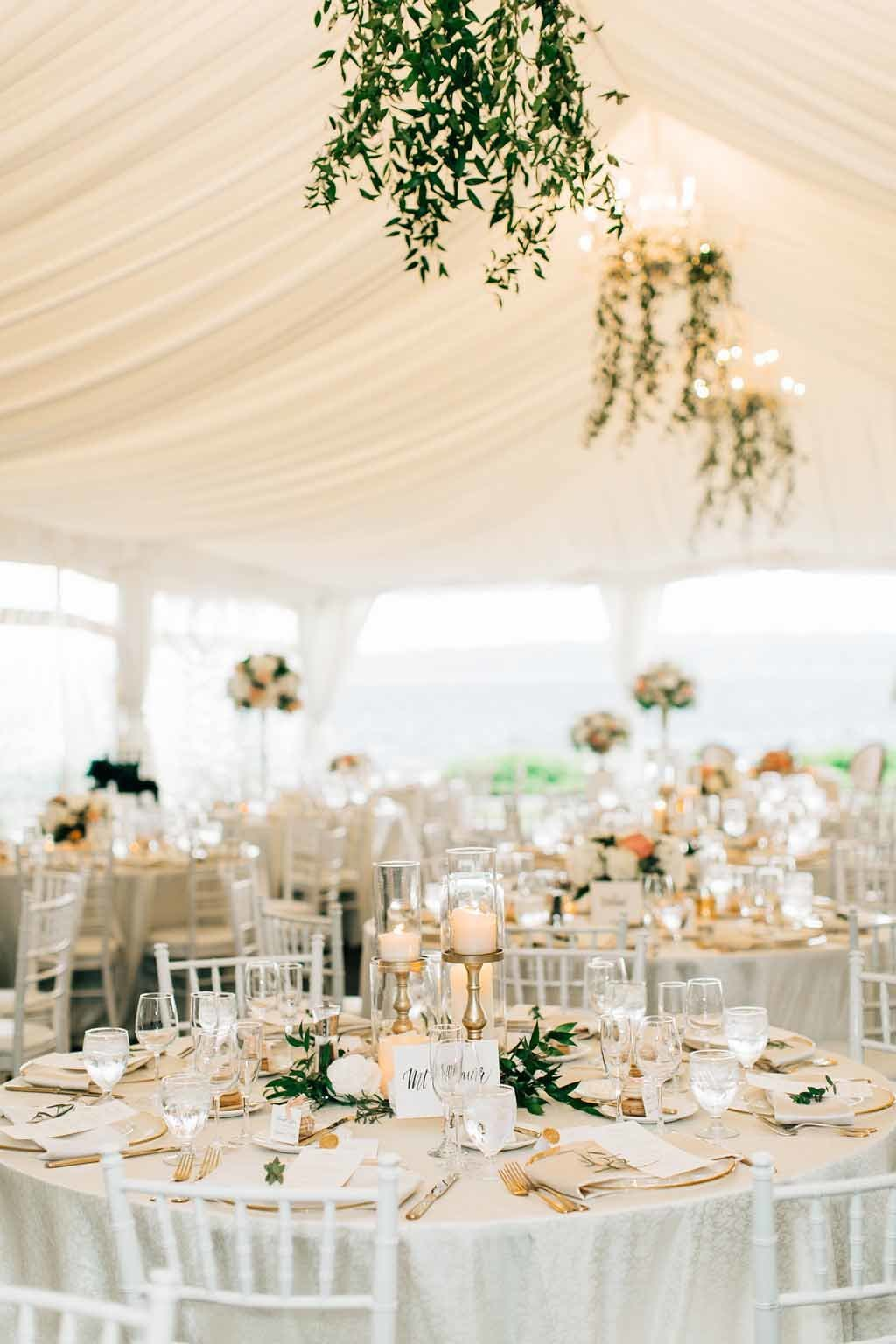 Elegant tent wedding reception at Woodmark Hotel with greenery chandeliers.