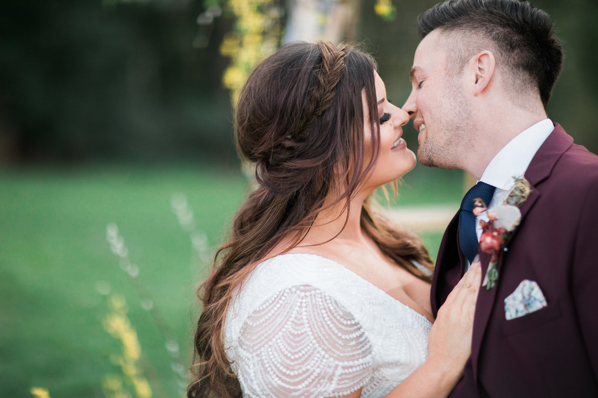 Wedding Photographer,  bride with wrap around braid and groom in win colored suit going in for a kiss