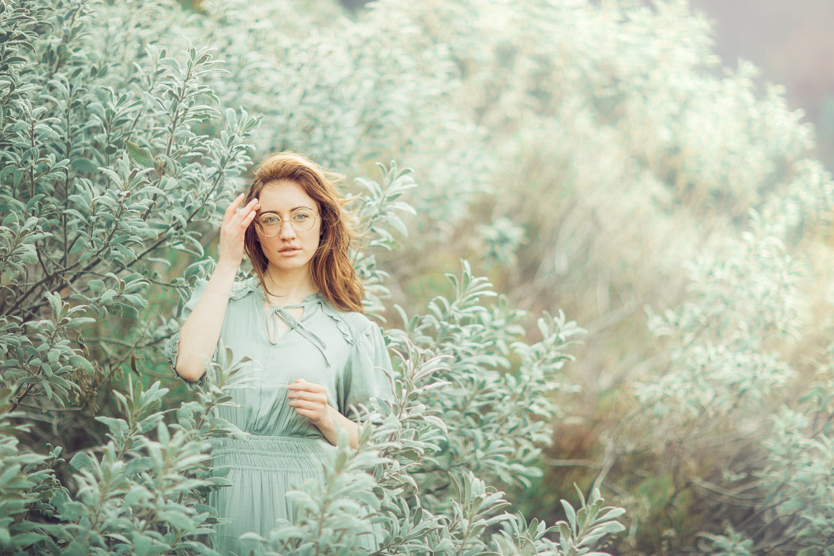 Girl posing amongst natural in beautiful mint green bush