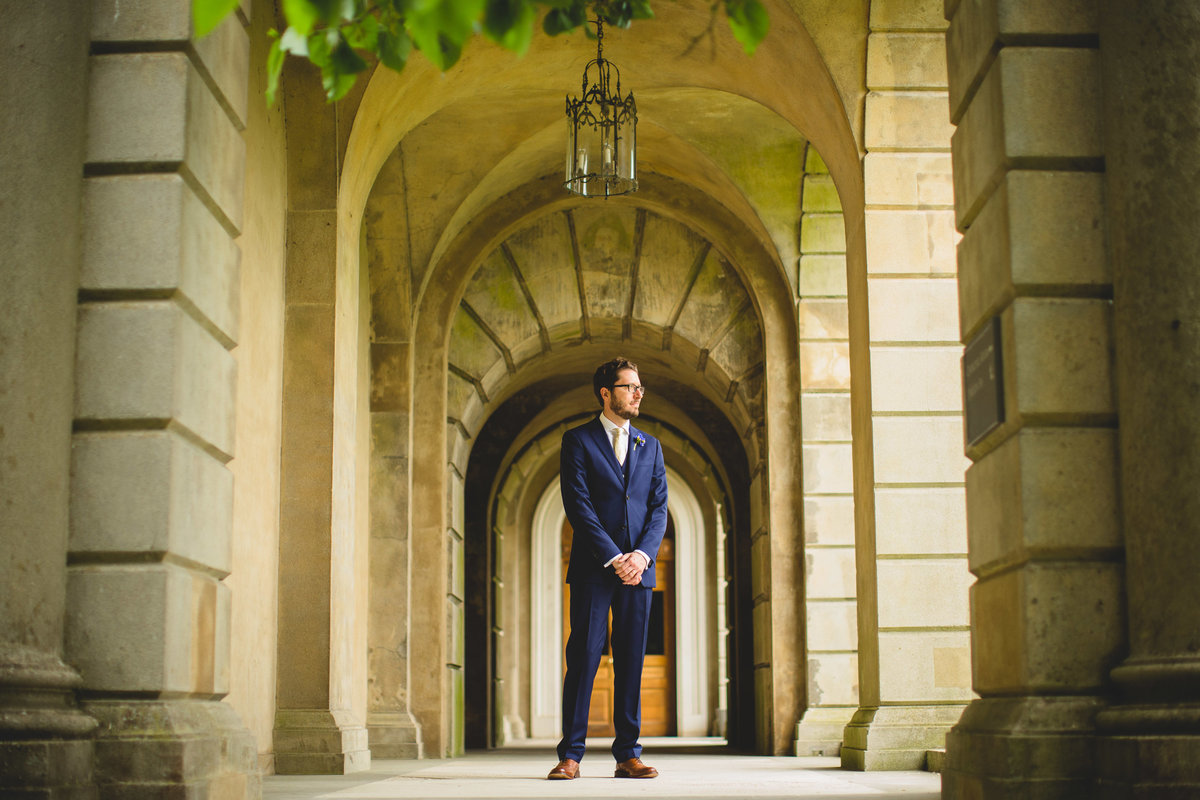 groom in blue suit at cliveden house standing in archway with leaves above