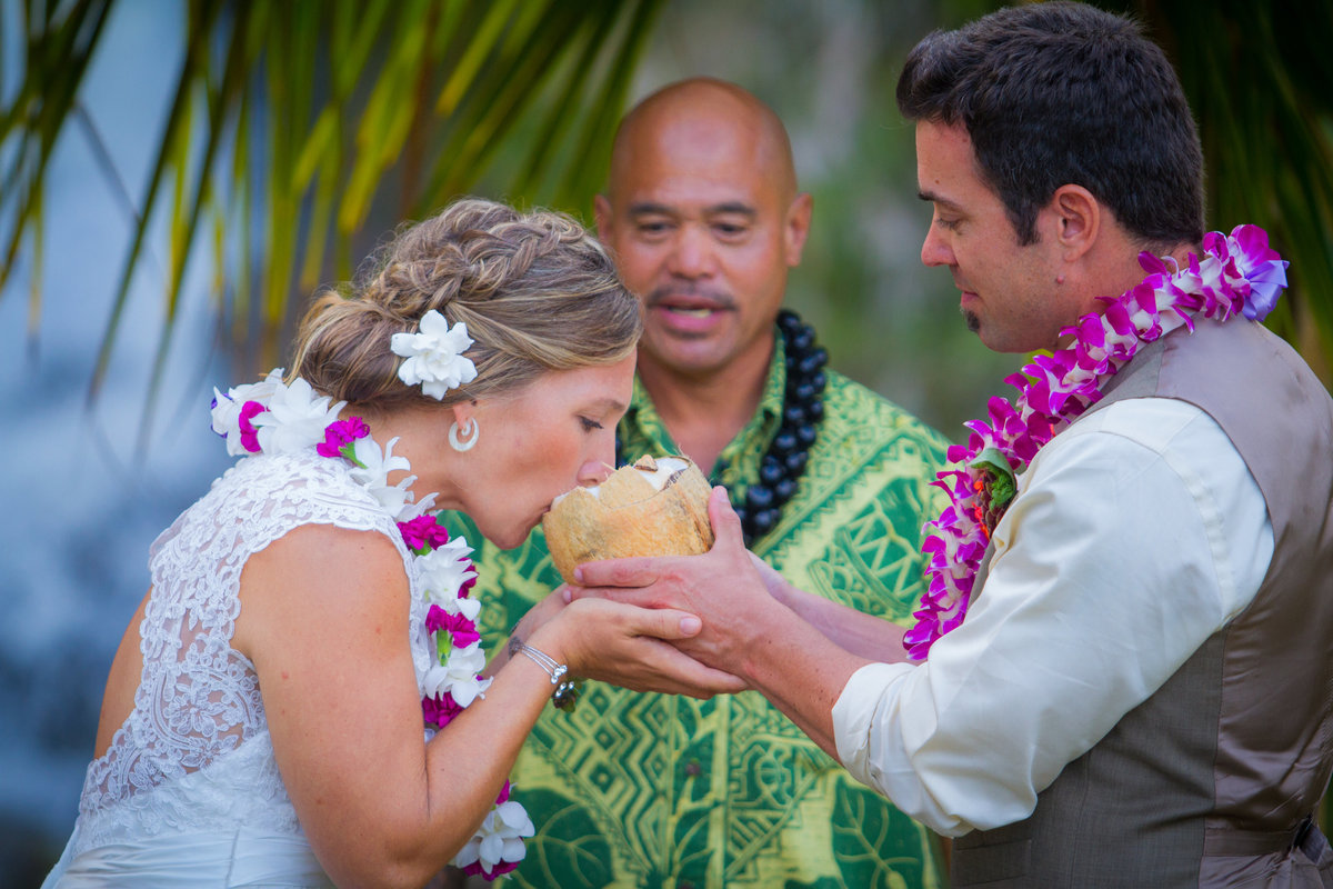 Wedding couple wearing leis share a coconut during their Kauai wedding ceremony.