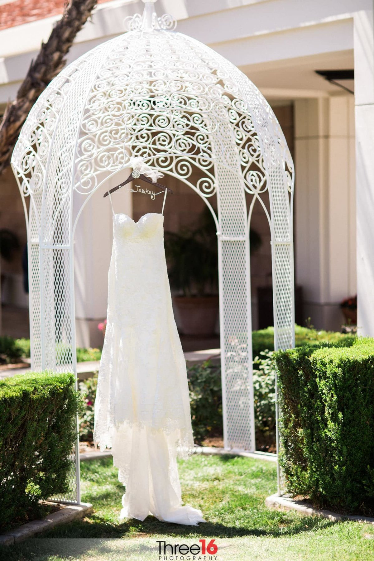 Bride wedding dress hangs on display under a small gazebo