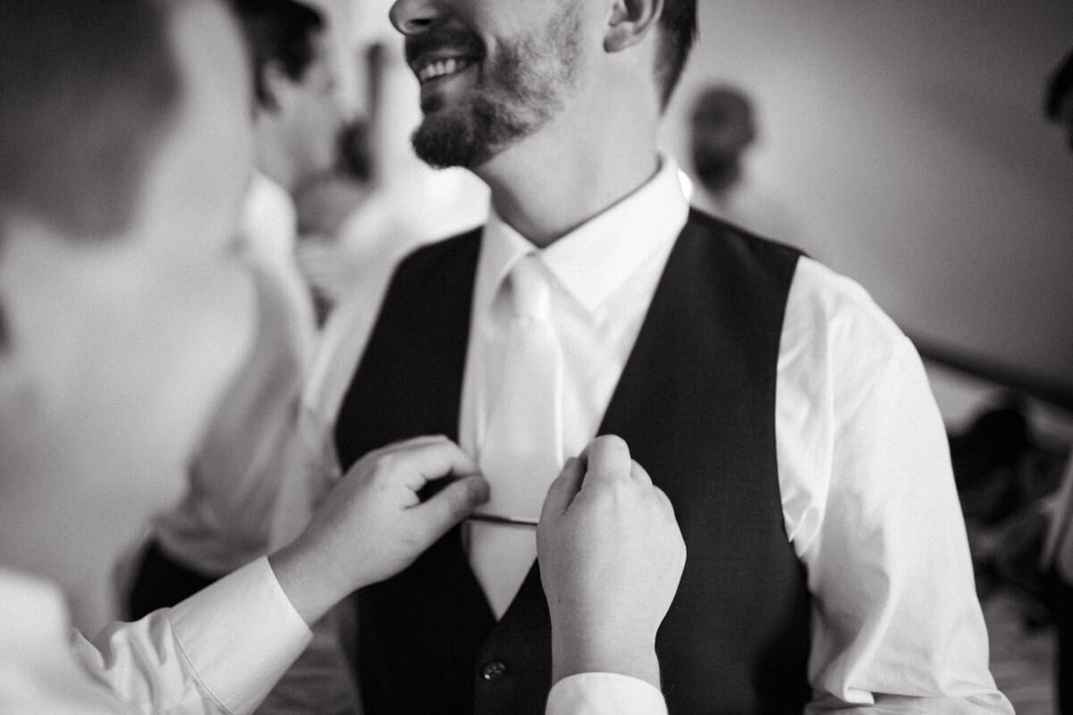 A man adjusts another man's tie in a black and white wedding photo