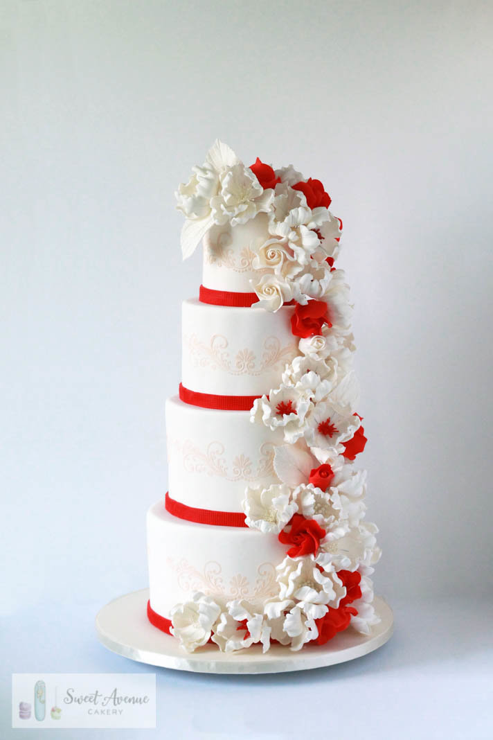 four tier white and red wedding cake with stencil lace and floral cascade