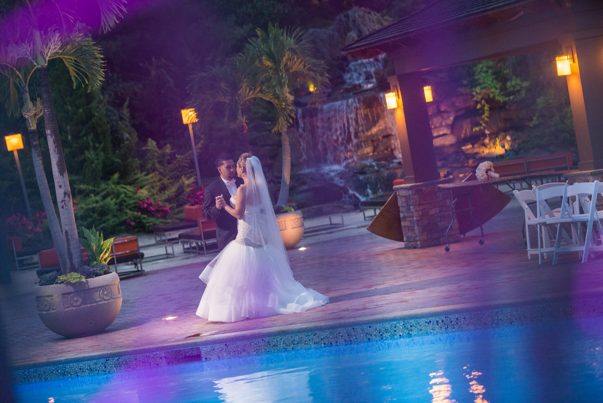 Bride and groom dancing by the pool at Crest Hollow Country Club