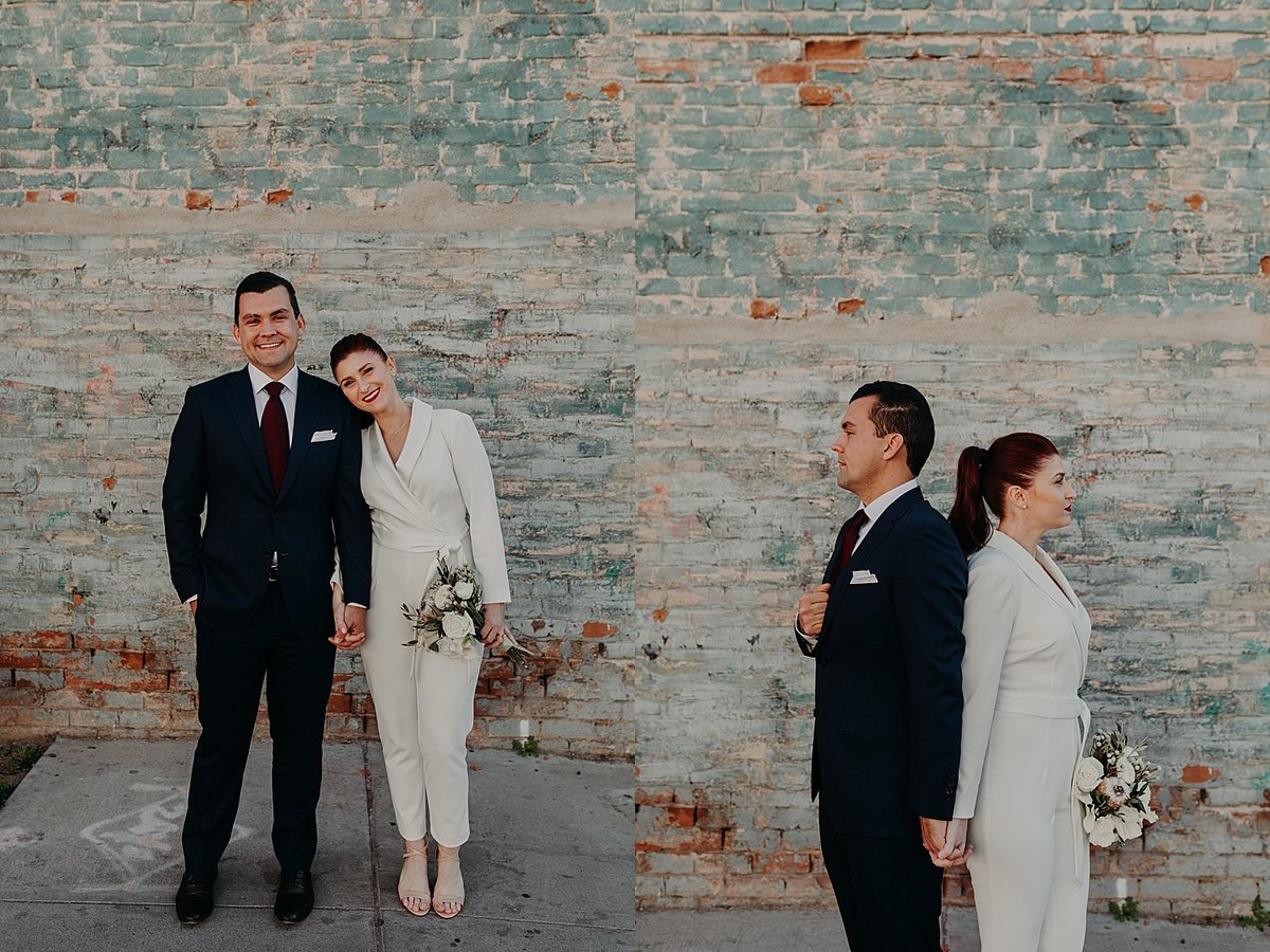 Bride wearing a white jumpsuit stands beside her husband in a suit and leans her head on his shoudler