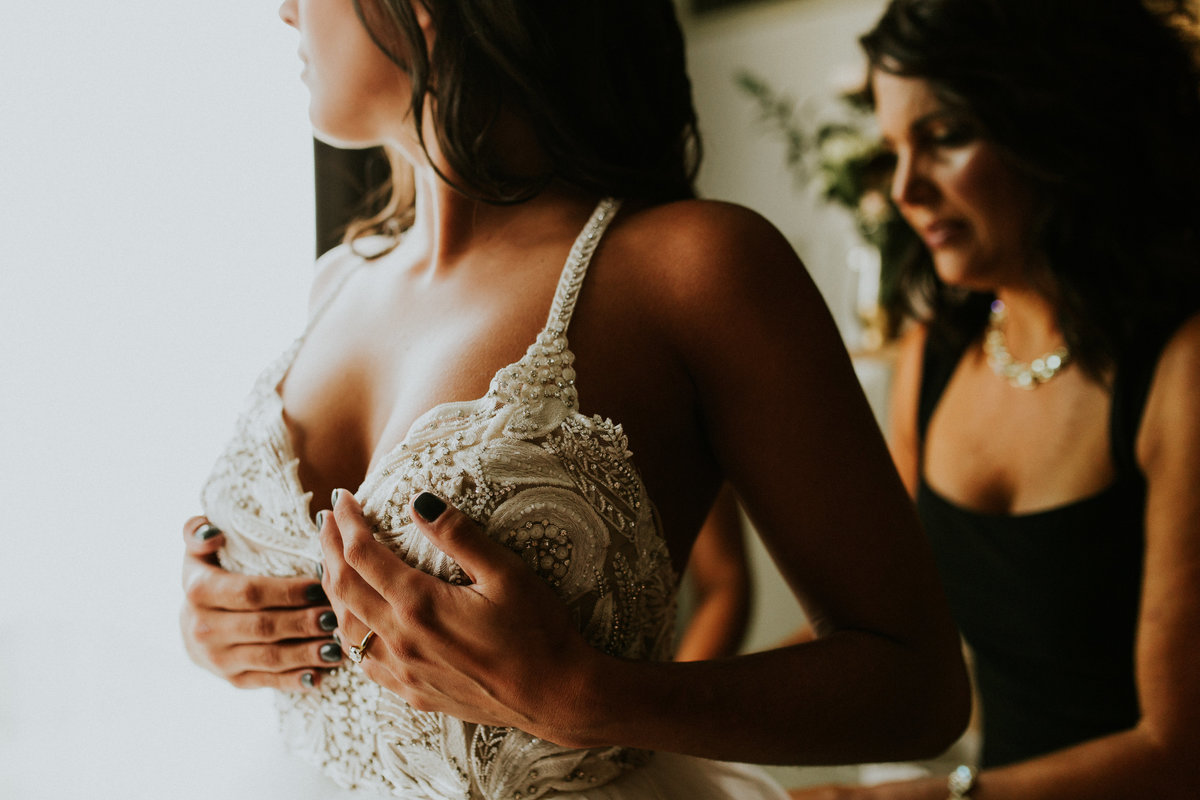 A bride gets her gown on as her mother helps