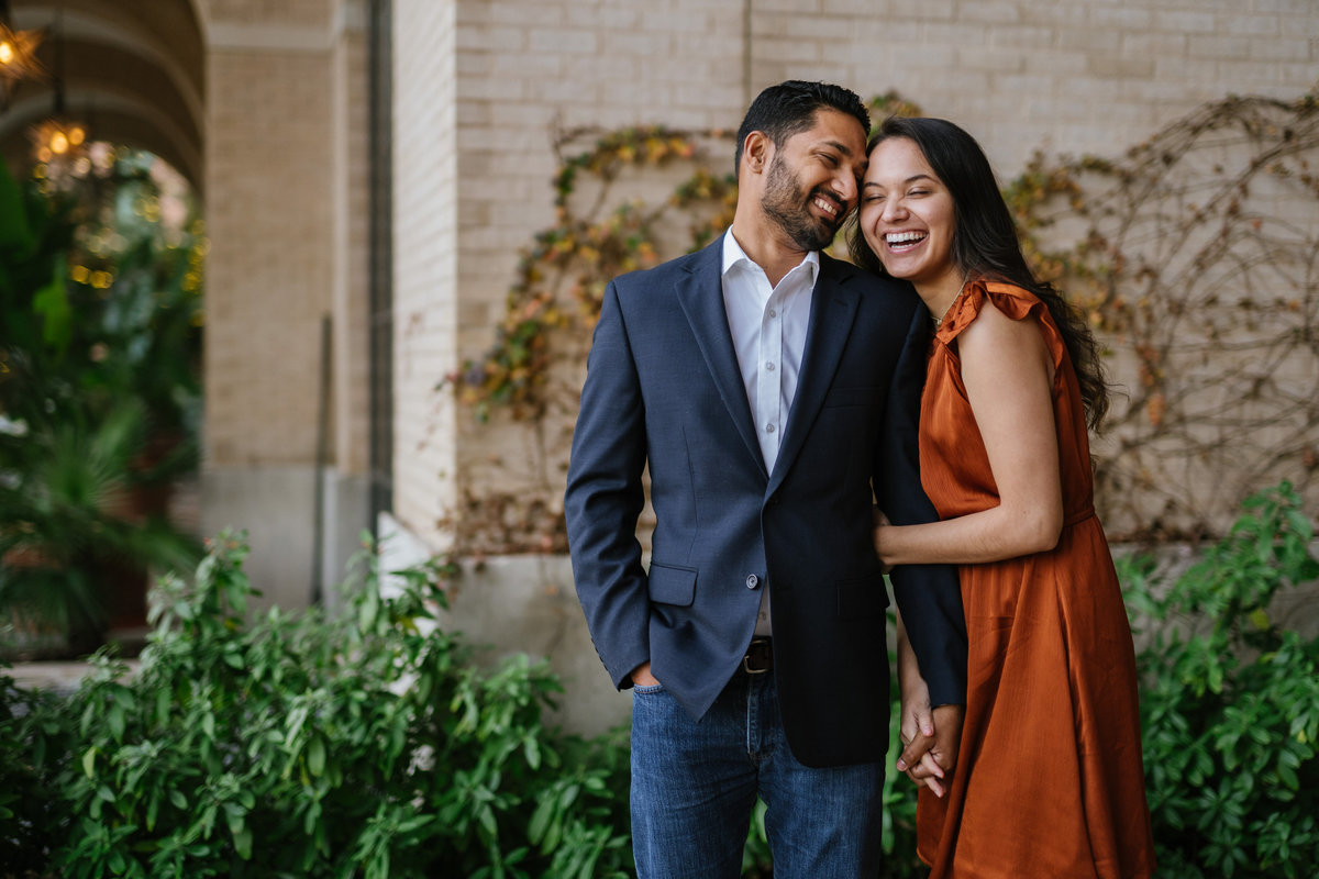 Smiling man and woman who are at their engagement photography session at the Historic Pearl in downtown San Antonio.