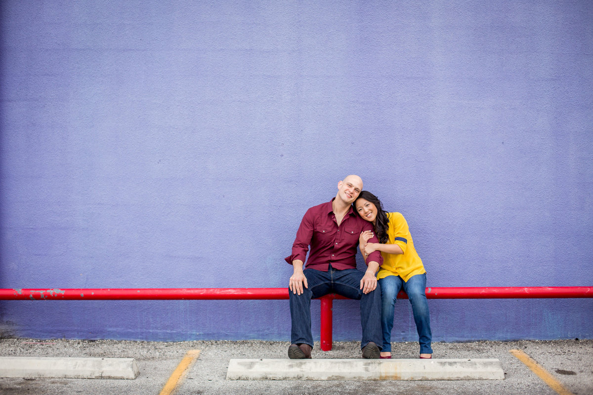 Happily engaged couple sitting on red rail in front of purple wall at Market Square in San Antonio