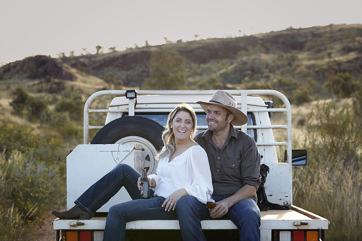 Young couple with beers in hand sitting on the back of the ute in natural bushland and with mountains in the backgroun