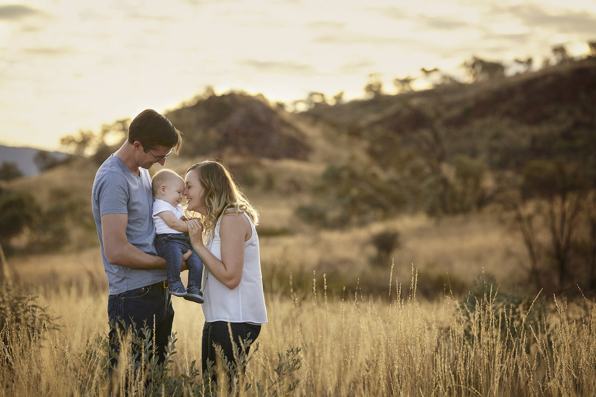 Couple with baby in field with golden light. Mum kissing baby on head and Dad holding baby