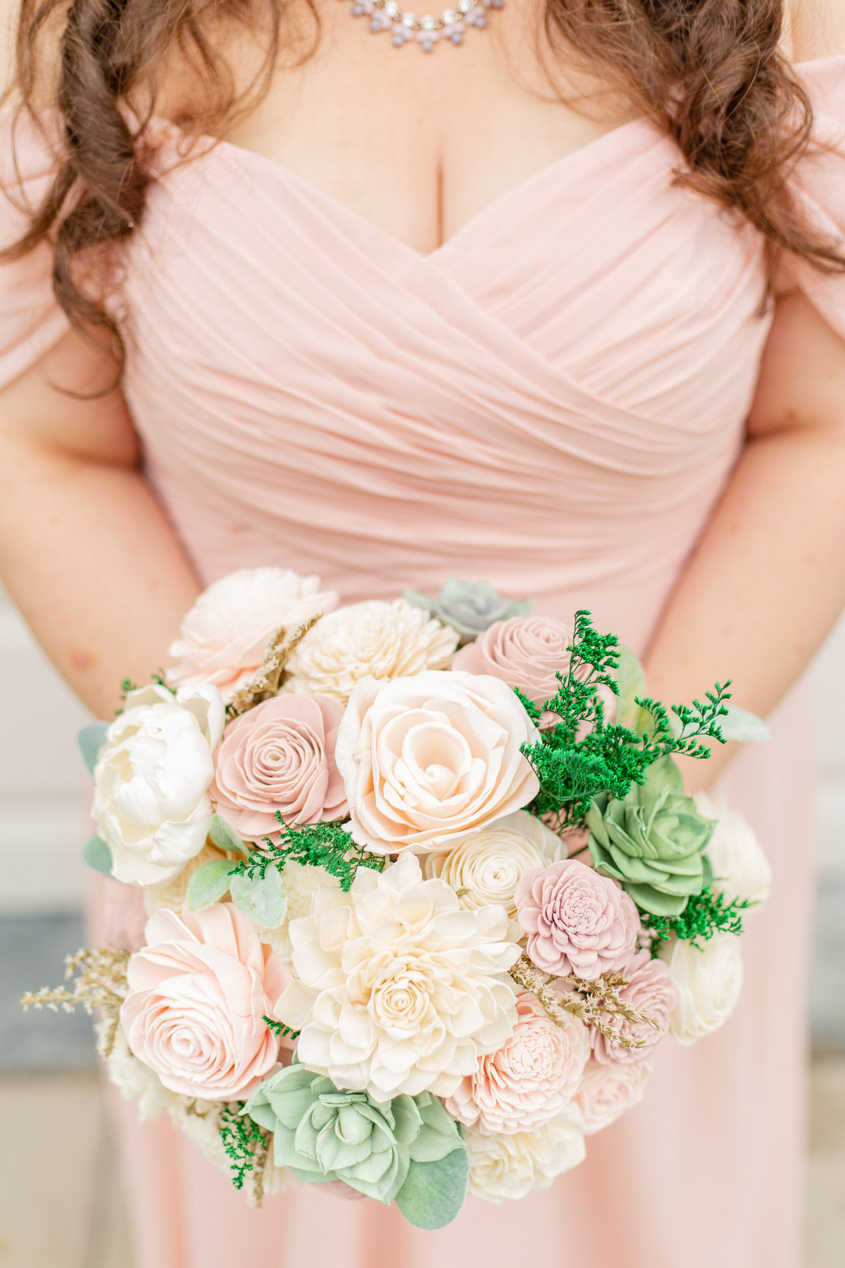 Bridesmaid blush gown styled with off the shoulder sleeves holds wooden green, blush and cream wedding bouquet