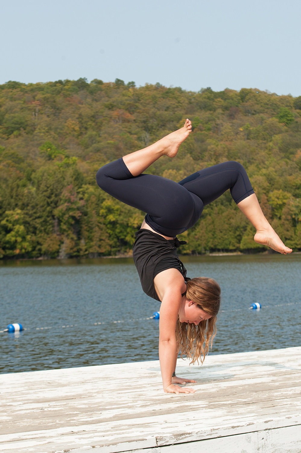 yoga woman doing handstand variation on dock