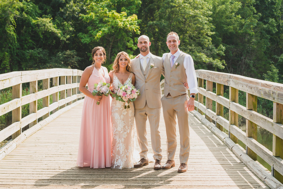 photo of bride and groom with maid of honor and best man on the bridge from beach wedding at Pavilion at Sunken Meadow