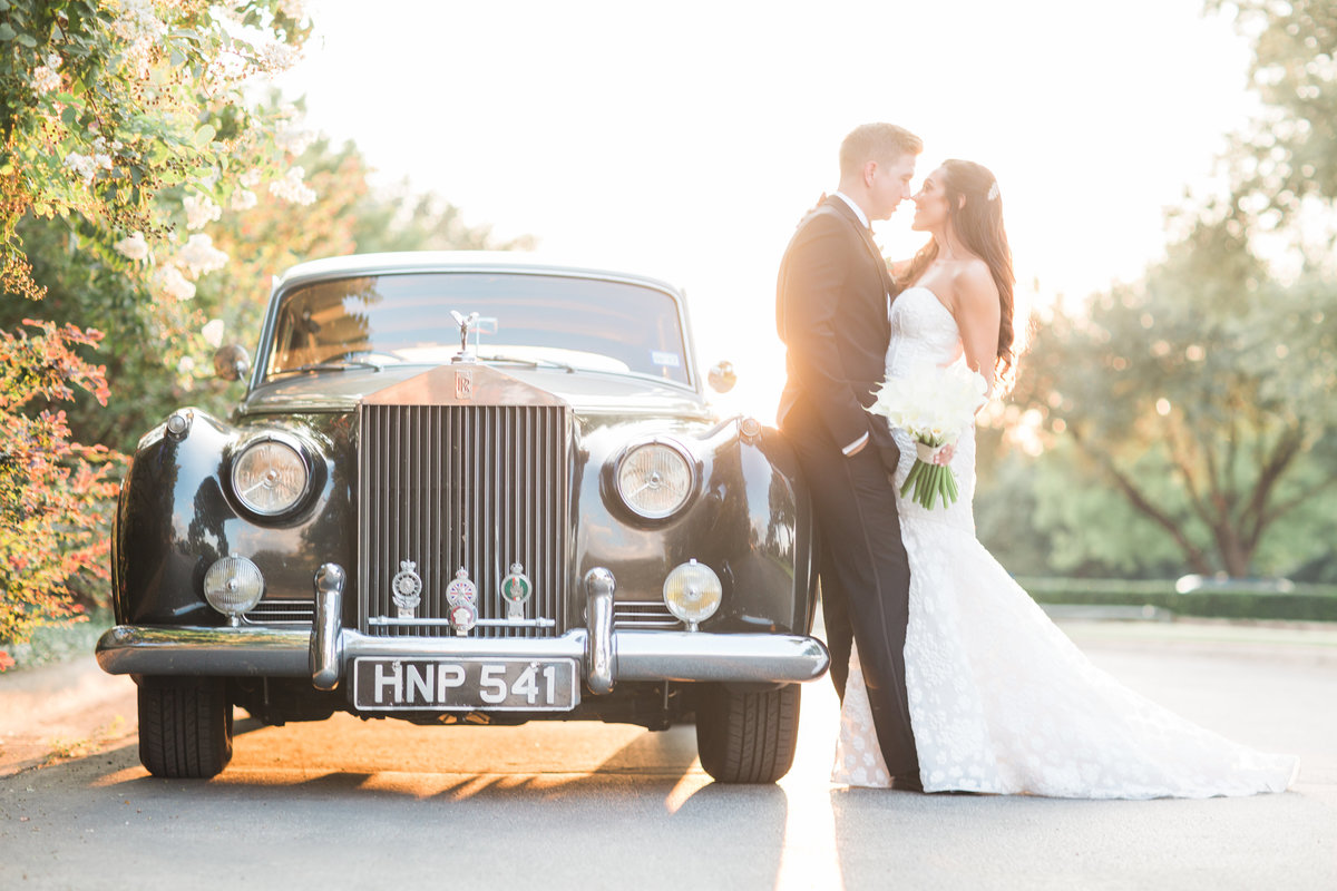 bride and groom portrait in front of vintage car at sunset
