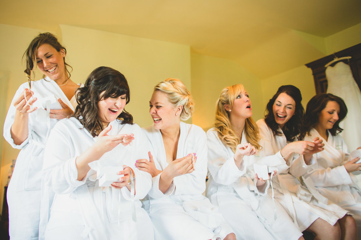 bridesmaids opening gifts on the morning of the wedding and laughing