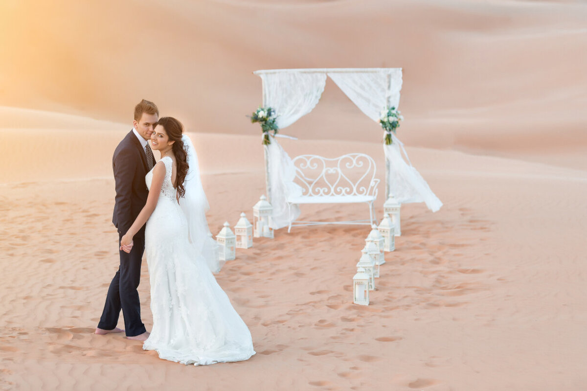 Wedding couple standing in front of wedding arch during desert elopement photoshoot organized by Lovely & Planned