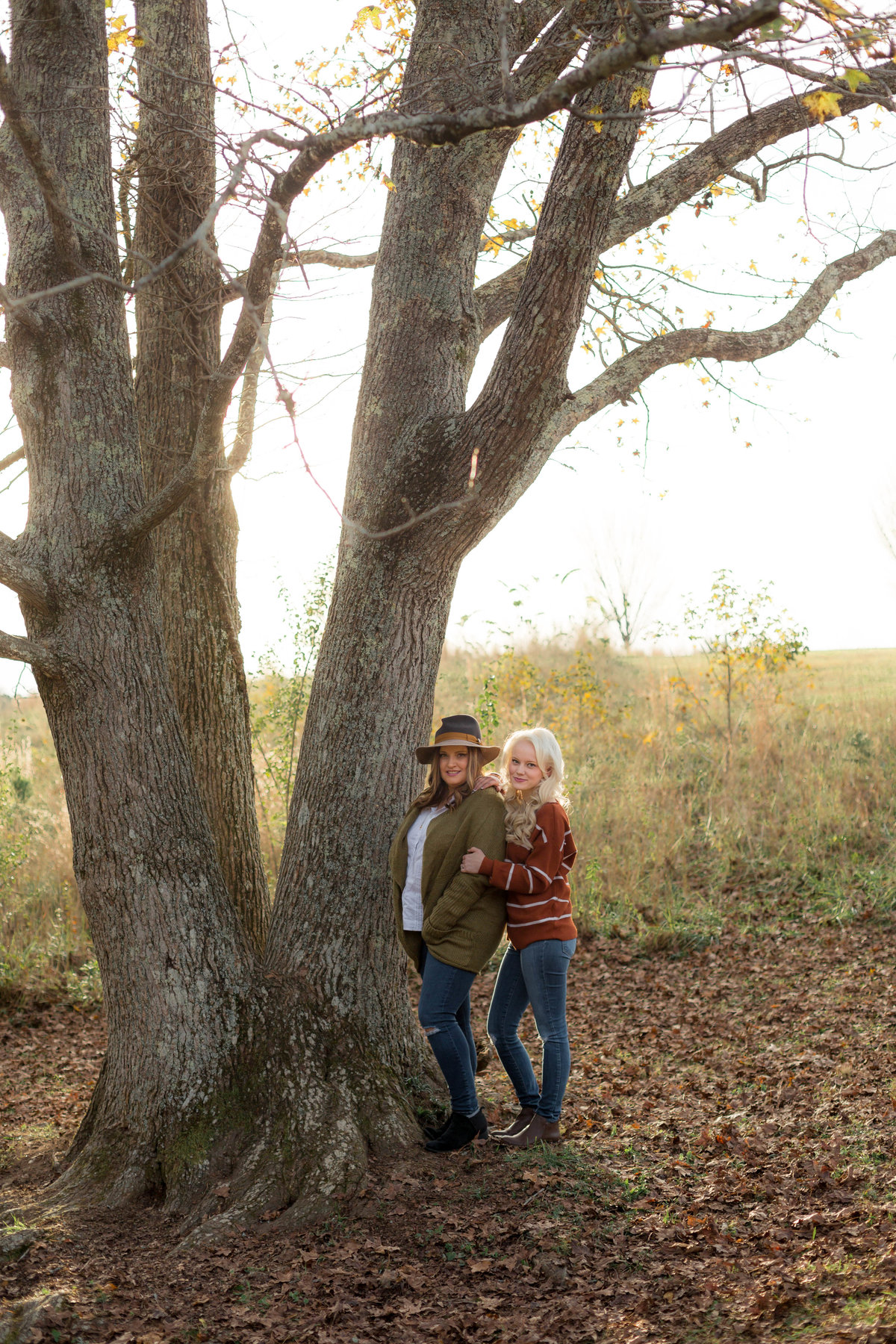 trendy engaged couple posing by tree for wedding photographer