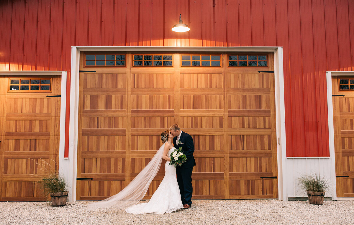 Bride and groom kissing in front of a barn door at their wedding venue