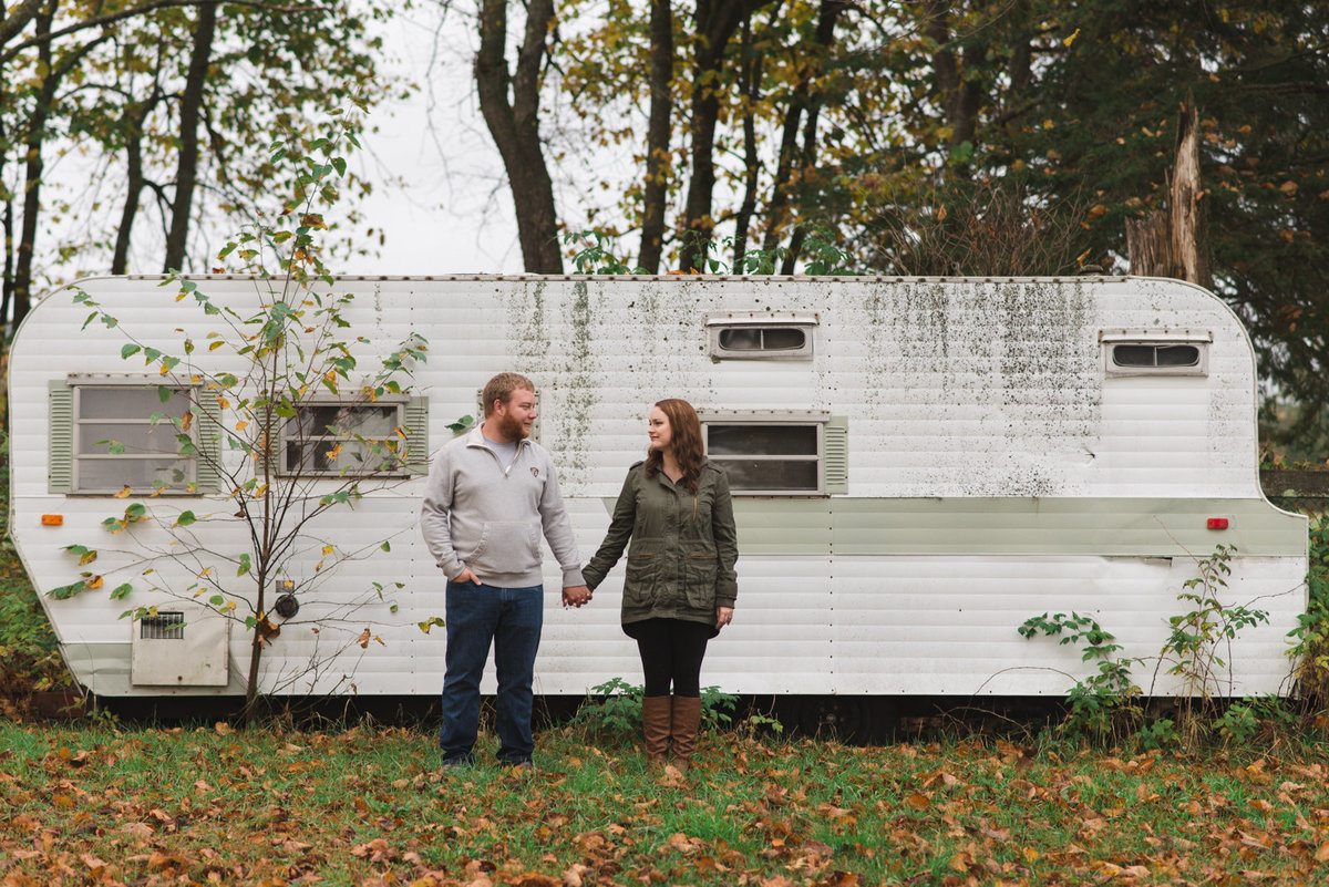engaged couple standing in front of old RV trailer holding hands