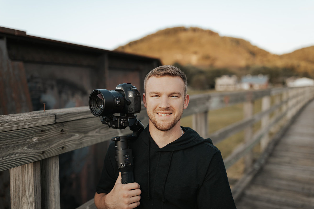 Tyler the second shooter holding a camera smiling at the camera