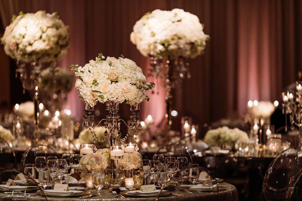 Big classic ballroom winter wedding, with white and grey floral arrangements on silver candelabras