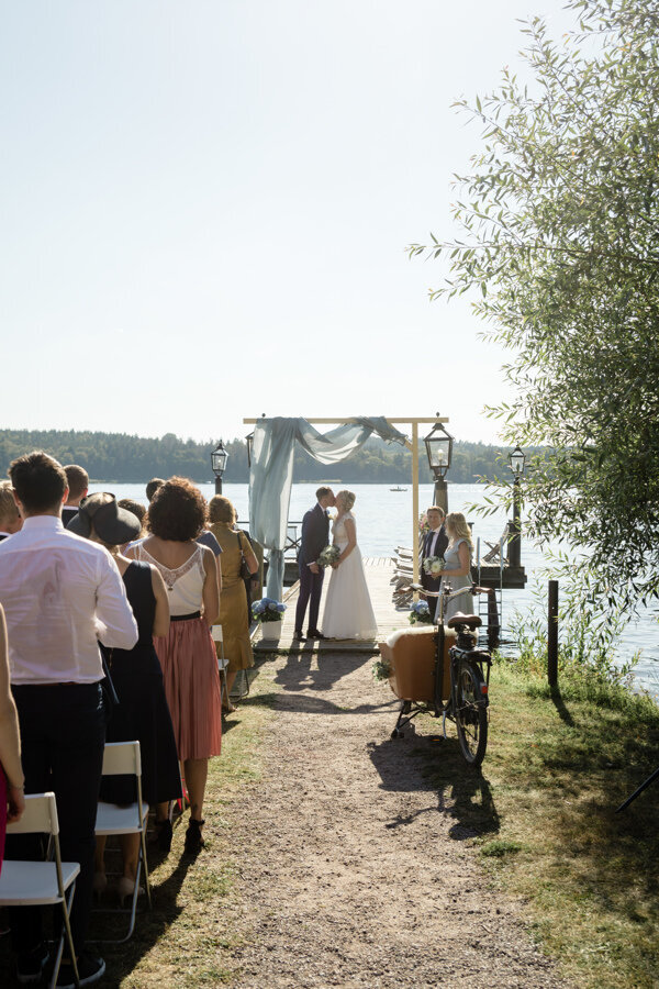 Bride and groom stand under altar with light blue fabric and kiss each other at outdoor wedding ceremony at Krusenberg Herrgård by the water