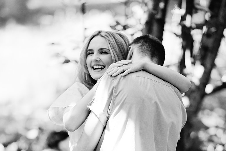 Smiling bride-to-be cuddling her groom-to-be