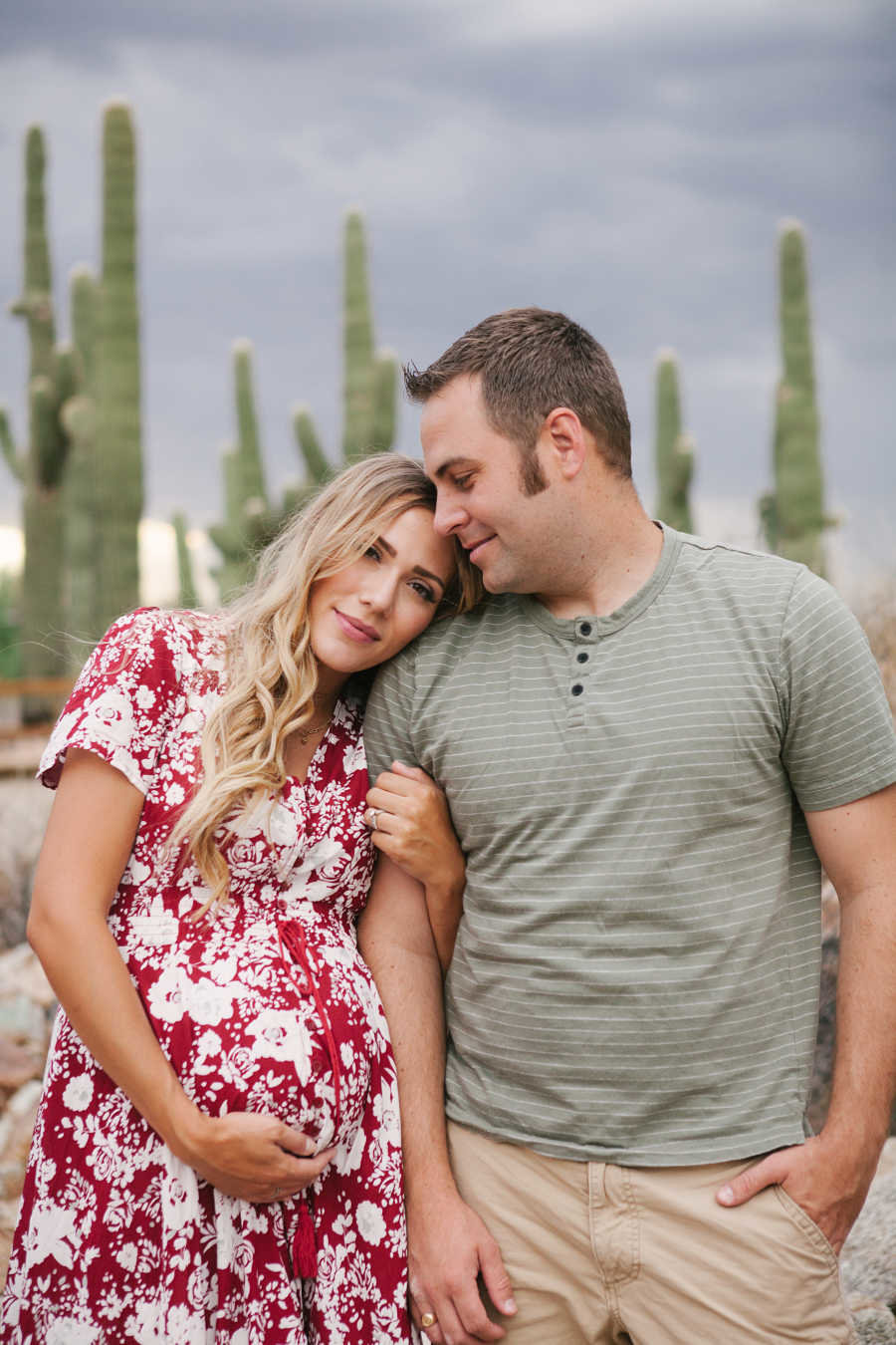 husband looking tenderly at pregnant wife in desert maternity photo shoot