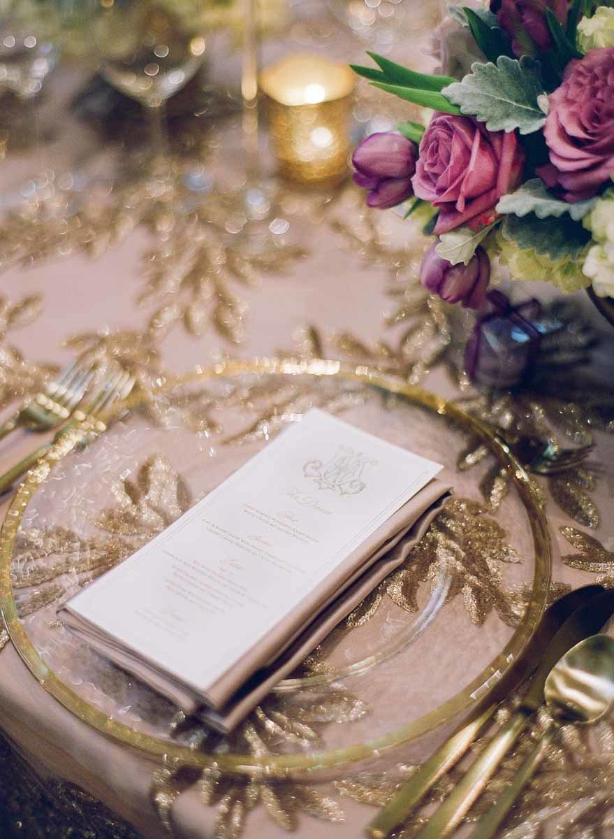 Elegant gold place setting paired with purple floral arrangements.