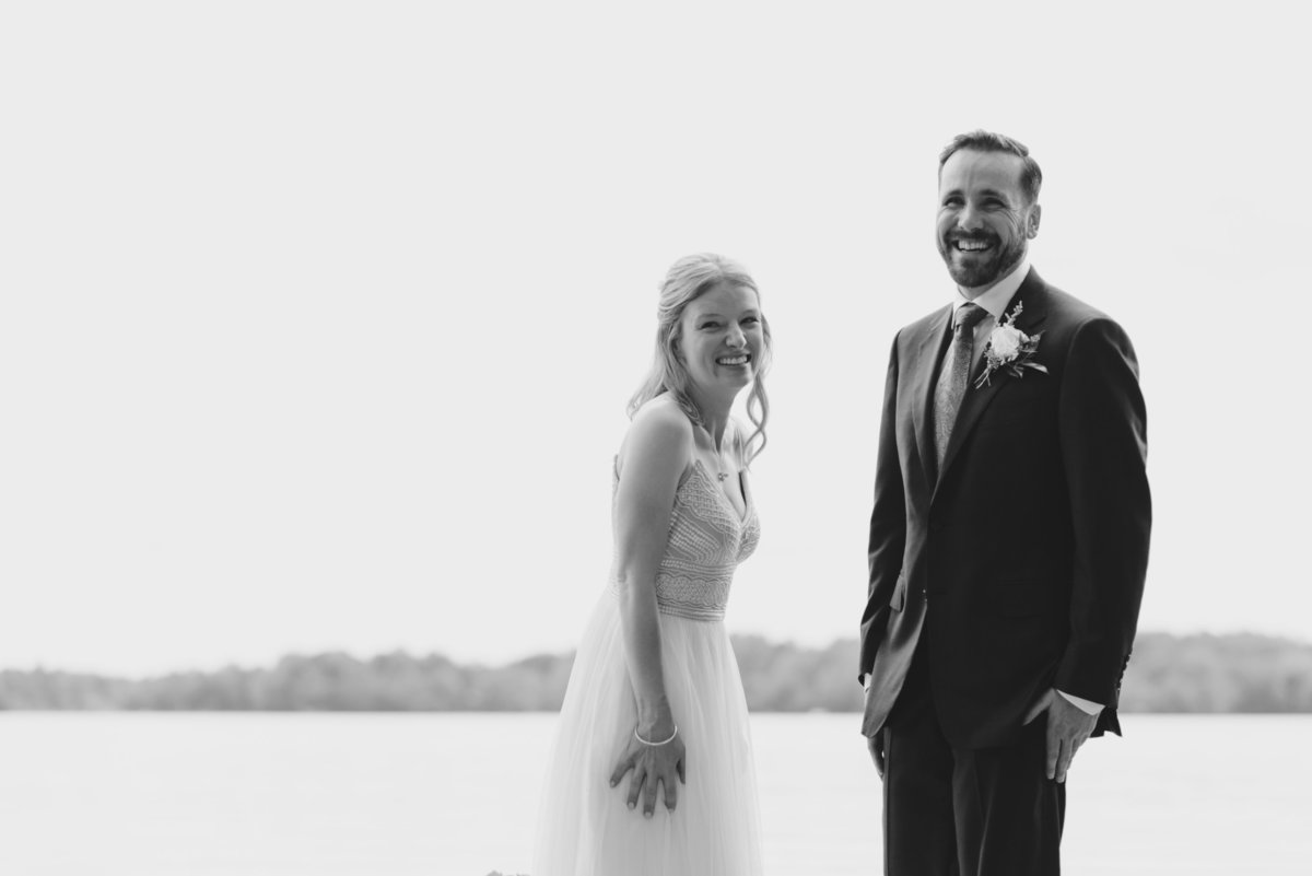 Bride and groom laughing by the water's edge at the cottage
