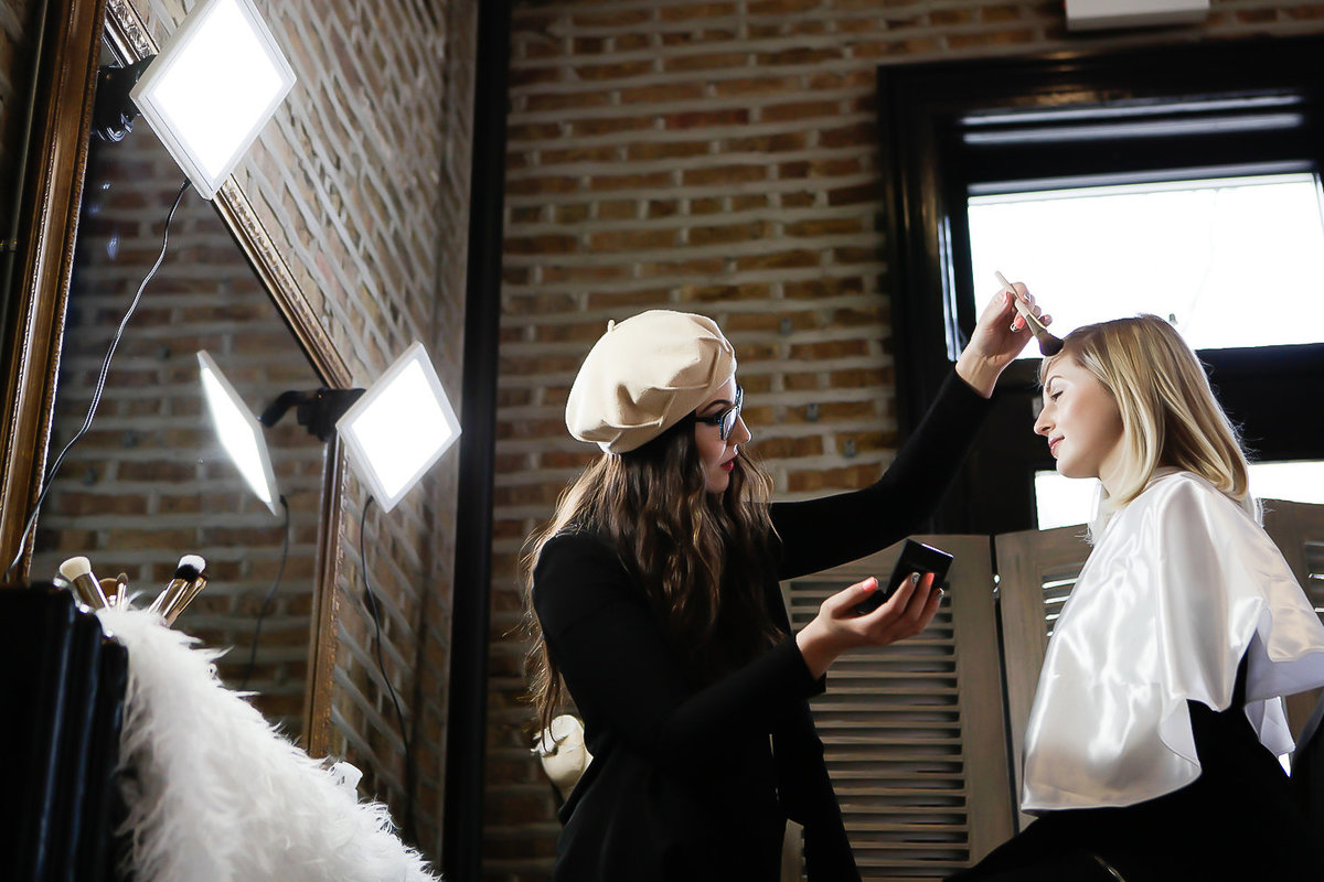 Makeup artist in a tan beret applies powder to young woman's forehead in a brick makeup studio