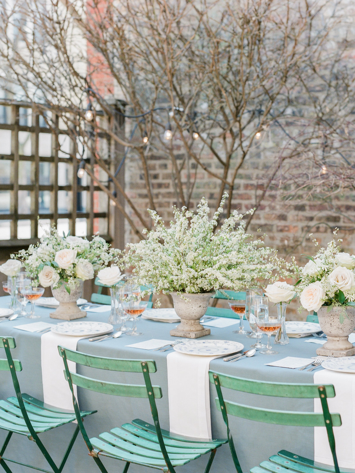 wedding table set with french blue tablecloth and green chairs
