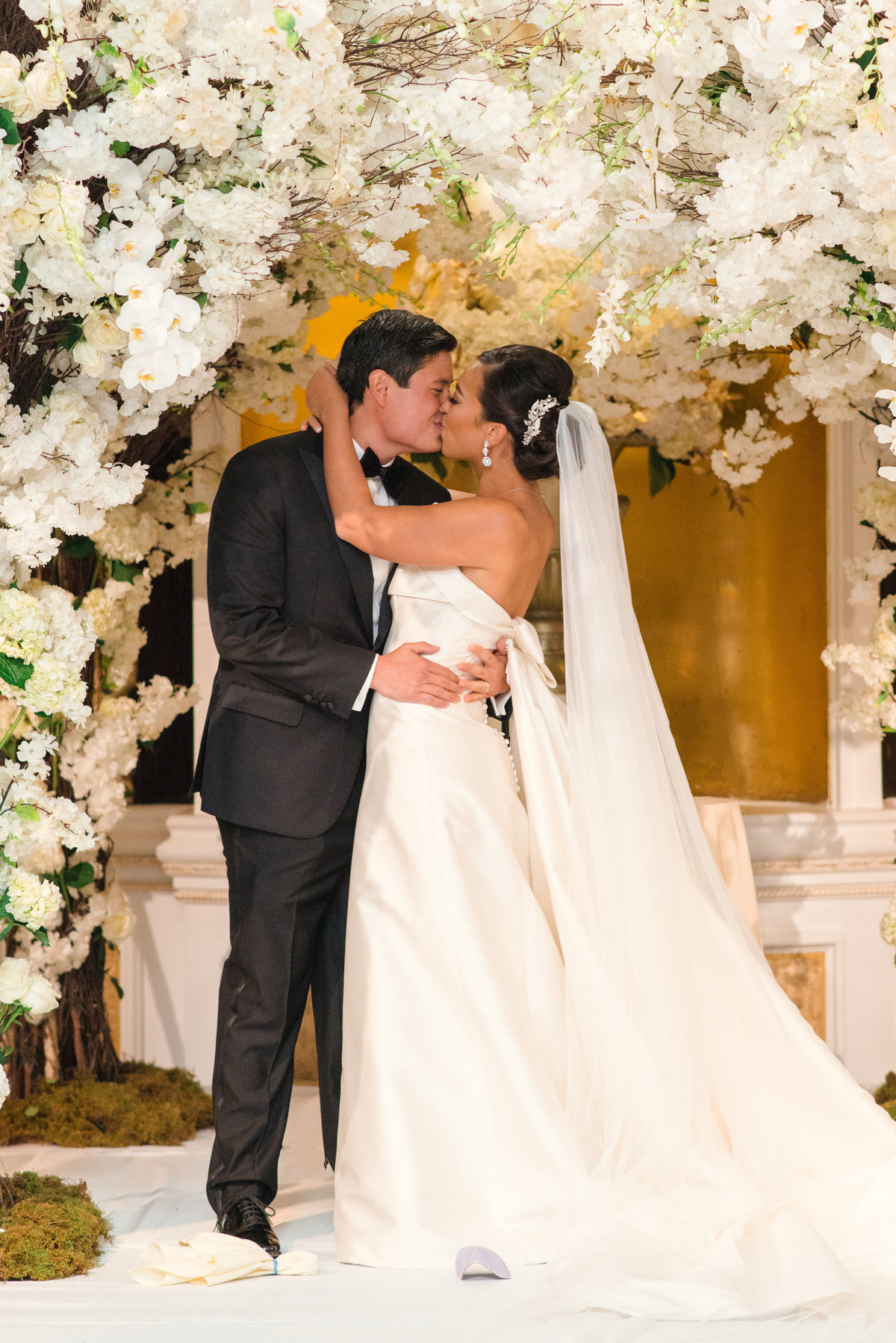 photo of bride and groom kissing under white flowers during wedding at The Garden City Hotel