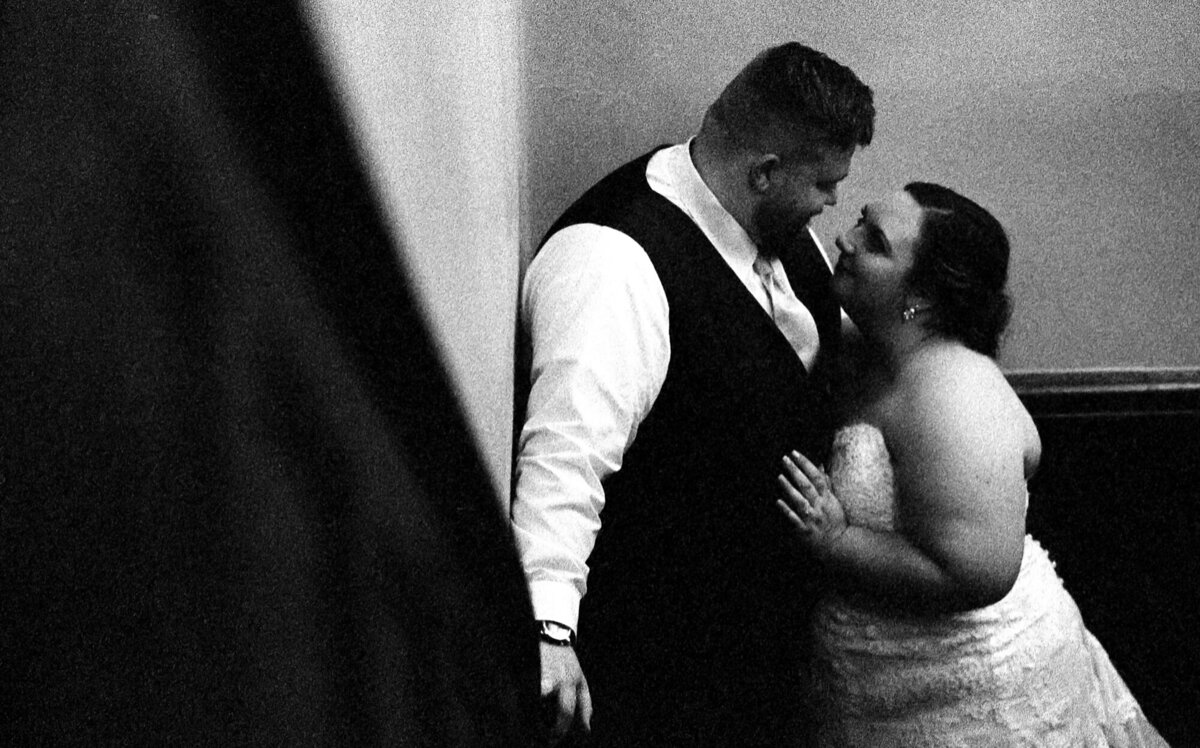 Couple snuggles in the stairwell during their wedding reception