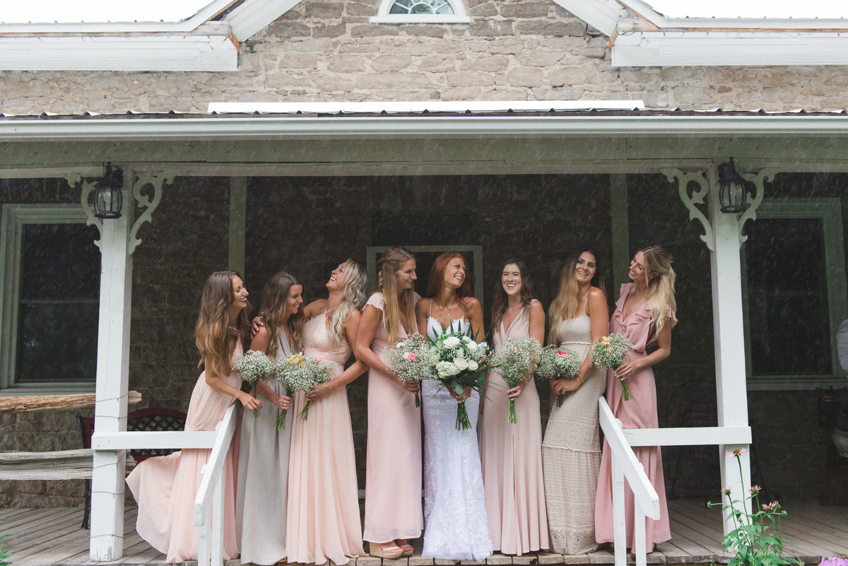 Bridesmaids in blush standing on the steps of old house