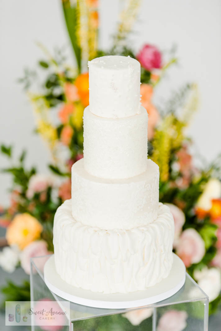 white textured fondant wedding cake with lace, fabric and glitter tiers