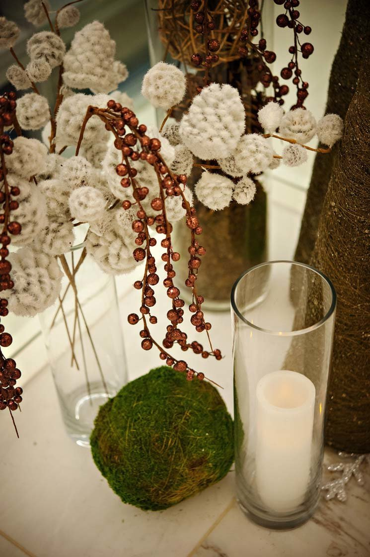 holiday decor with flocked branches, moss ball, hurricane candle, gold tree cone
