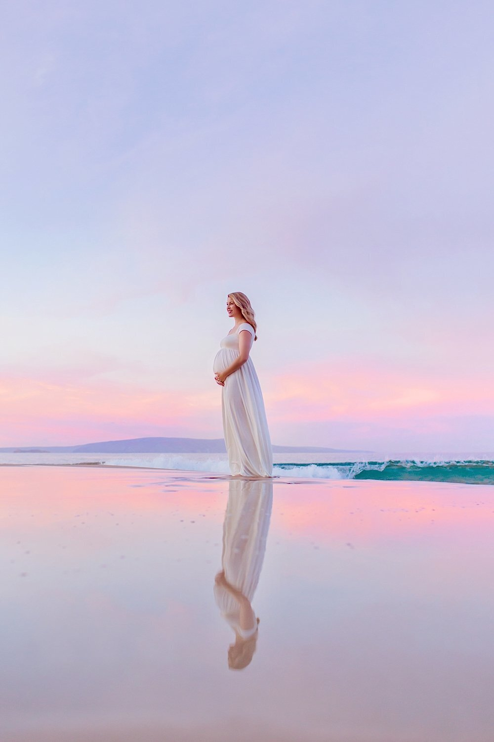 Pastel tones at sunrise, pregnant mother holds her belly and looks out to sea