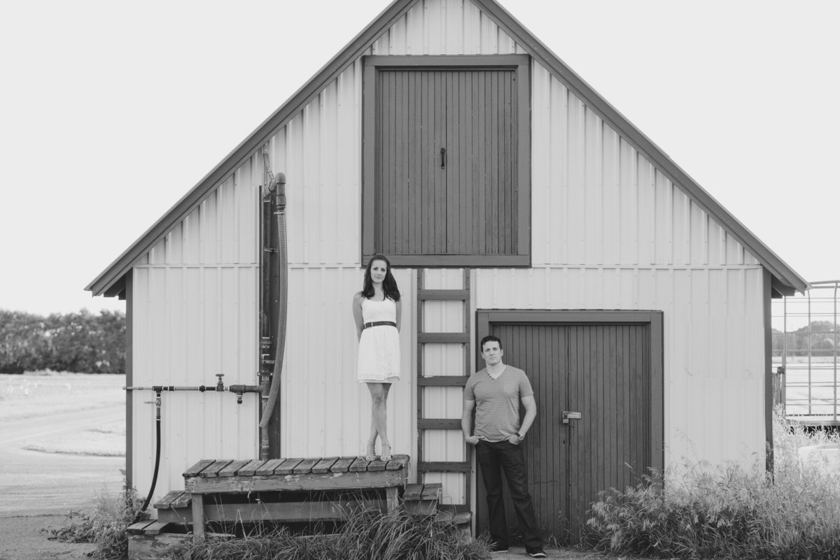 couple standing in front of old barn with ladder at experimental farm