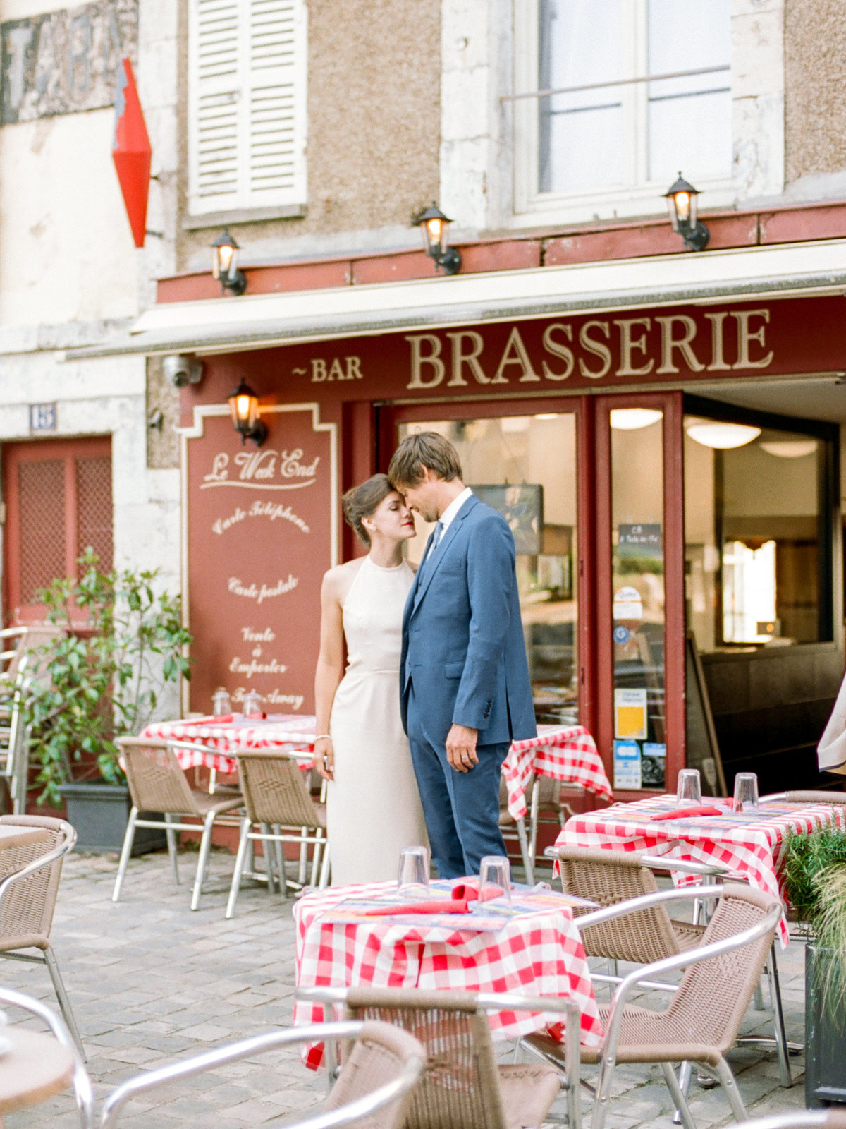 couple standing in front of french brasserie