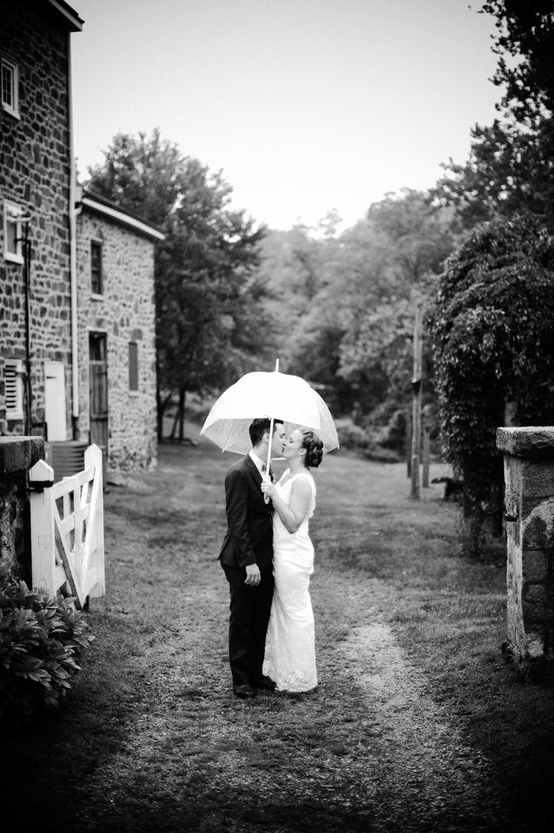 Couple under an umbrella during their rainy day wedding in PA