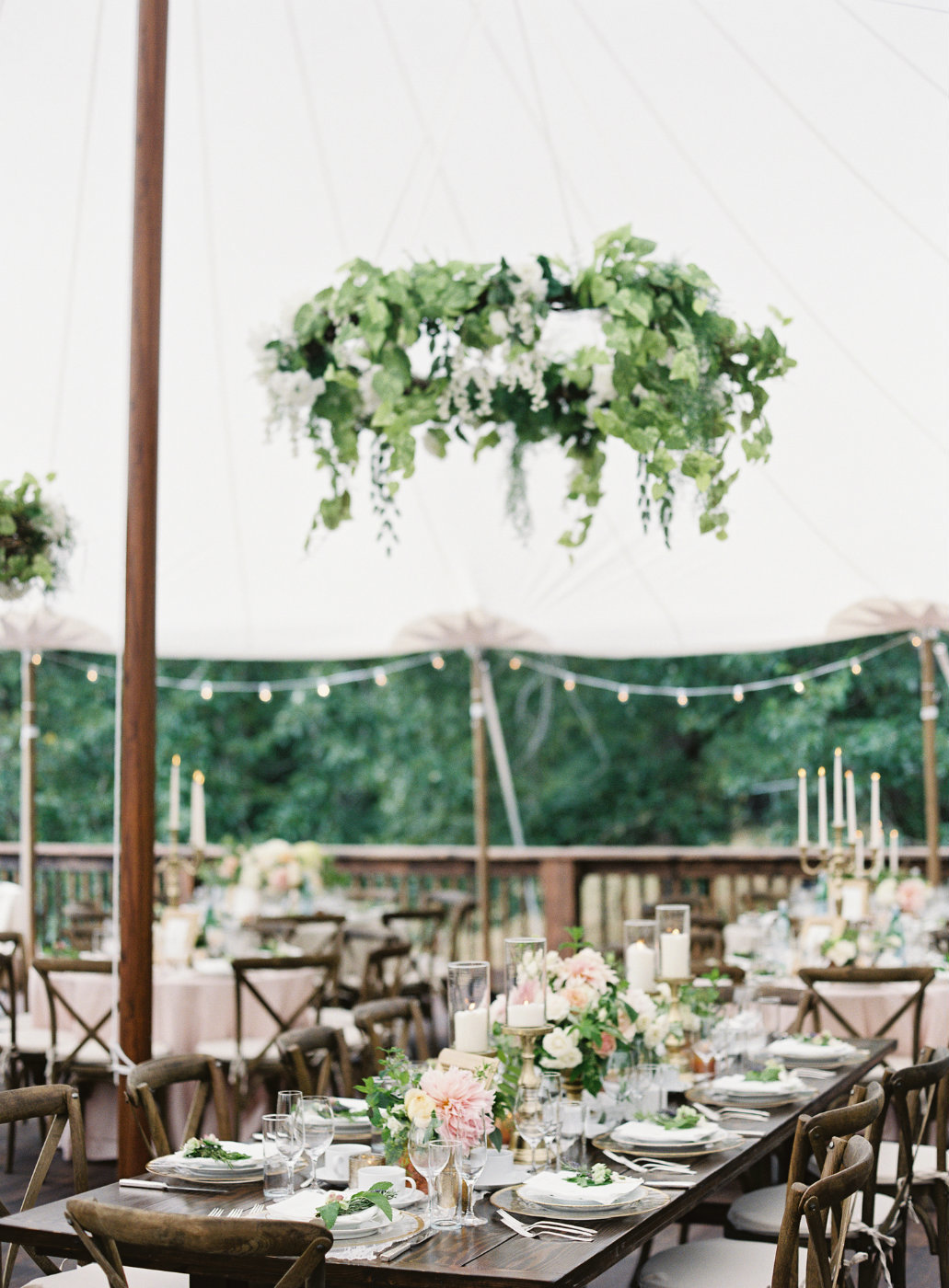 Garden tent wedding with  large floral wreath hanging installation and long wooden farm table lined with flowers and candles.