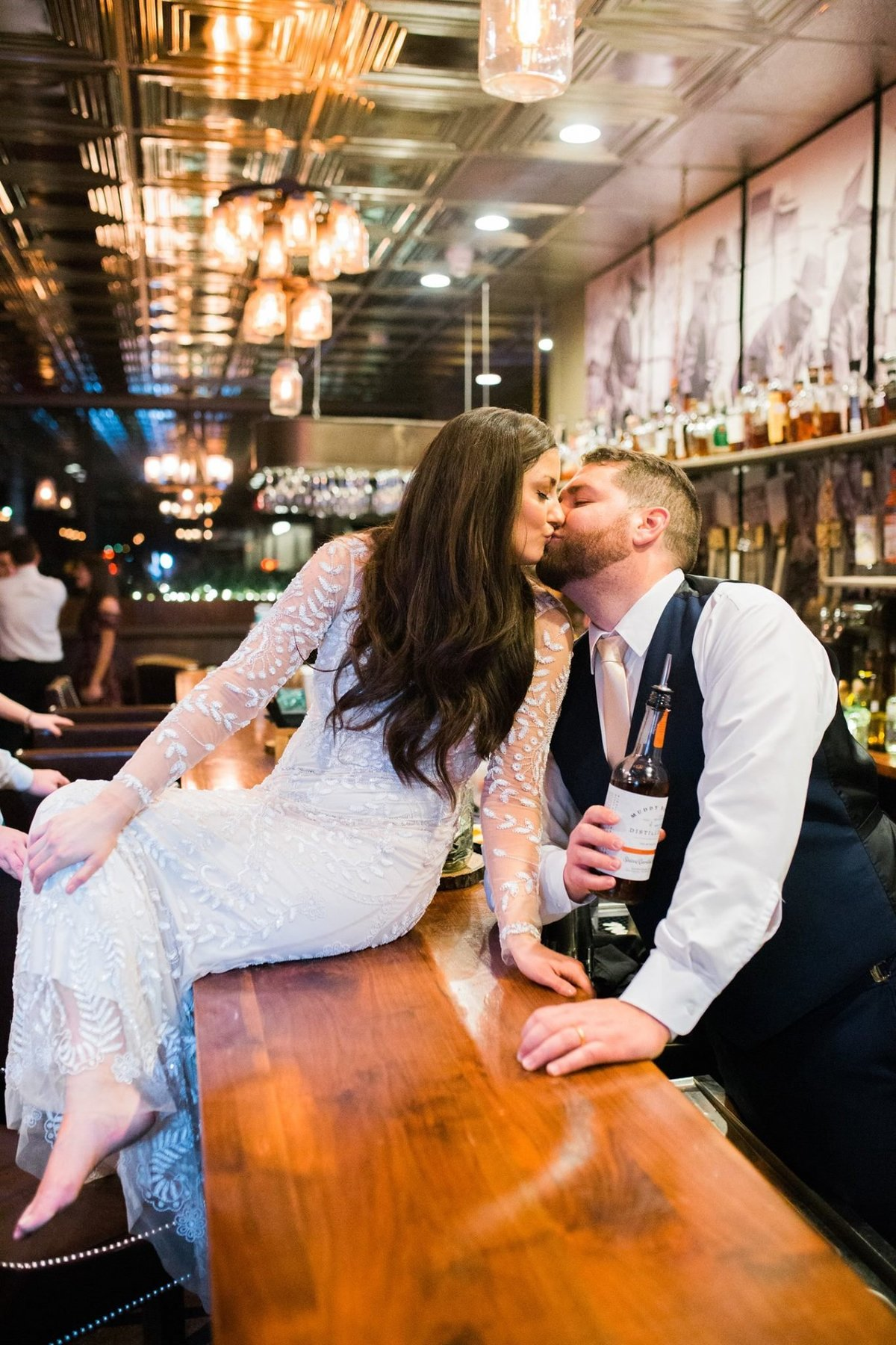 Wedding Photographer, bride sitting on bar kissing groom