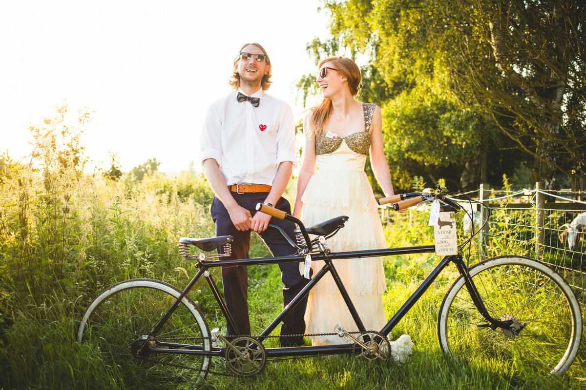 bride and groom with tandem bicycle in a field at sunset