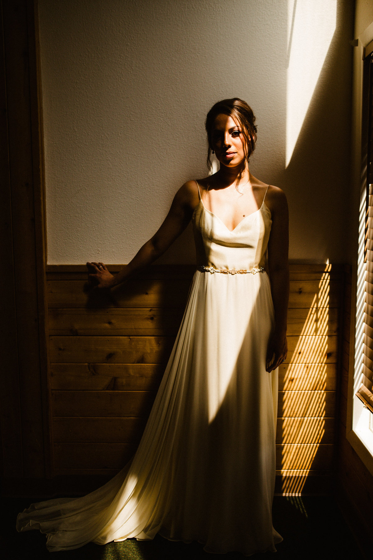 bride stands in stark sun patch of light at otter lake lodge