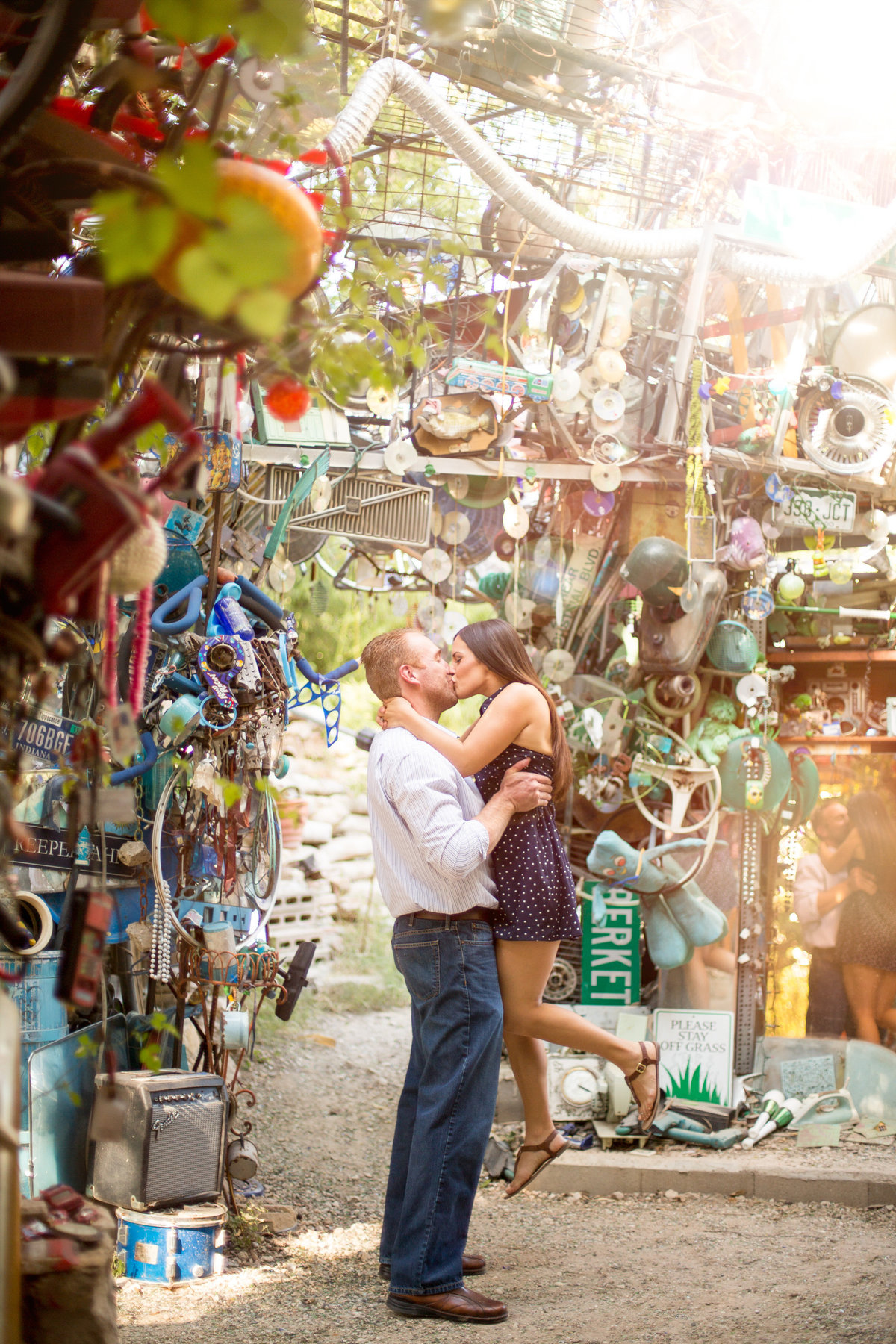 Fiancé lifting his fiancée up and kissing her at the Cathedral of Junk in Austin, Texas.