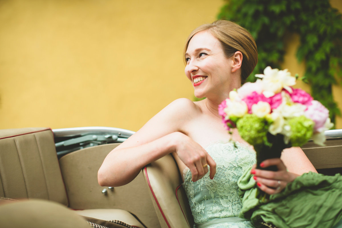 bride with flowers in convertible austin healey car looking backwards and smiling. yellow wall and ivy background.